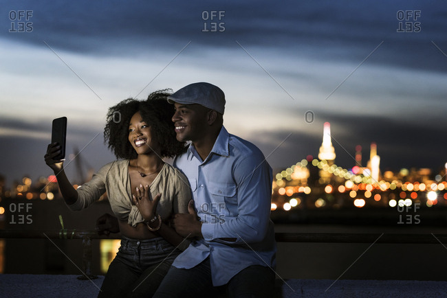 Fashionable couple taking selfie on smartphone while sitting on terrace railing in illuminated city