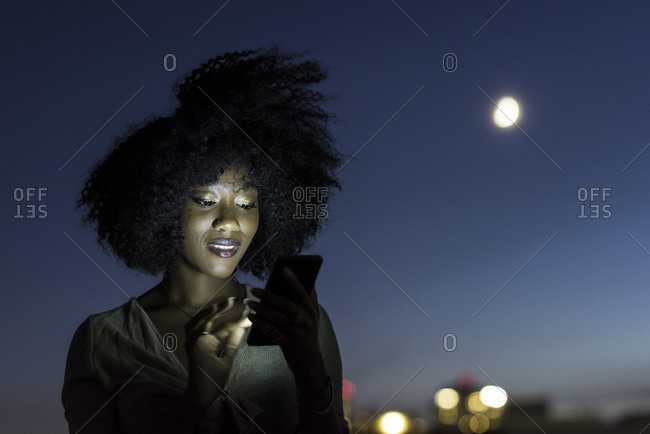 Beautiful young woman with curly hair using smartphone against sky at night