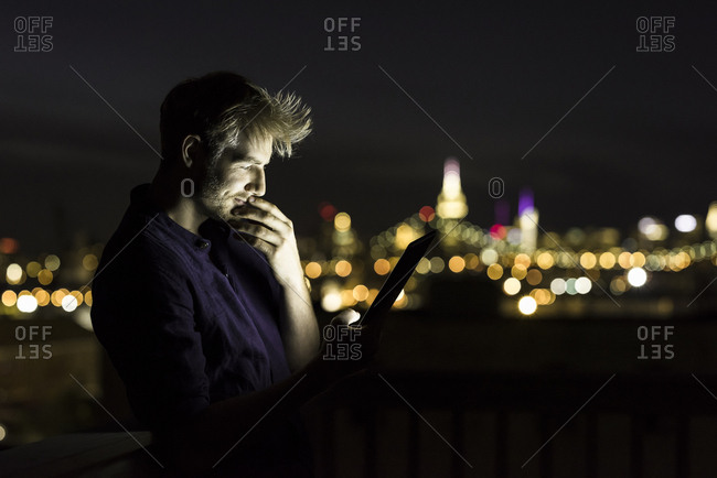 Side view of handsome young man using digital tablet on building terrace in illuminated city at night