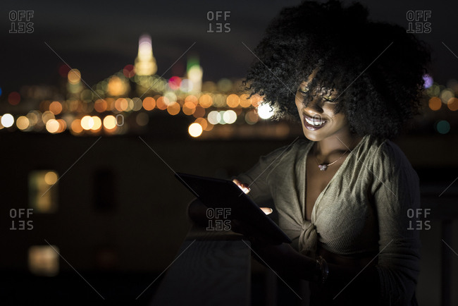Smiling young woman using digital tablet on building terrace in illuminated city at night
