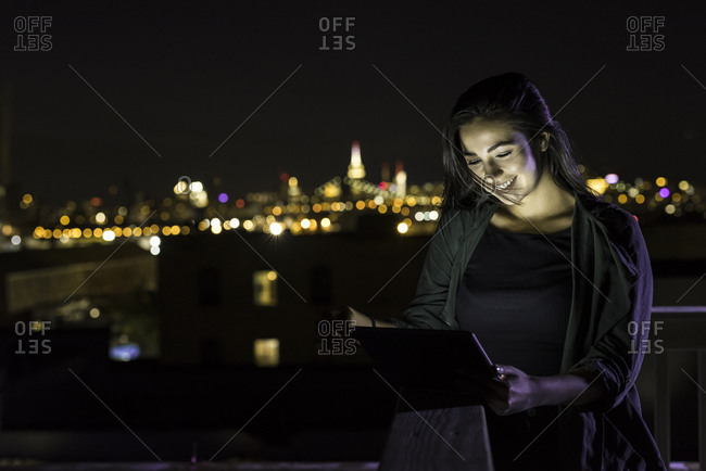 Attractive female having video call on digital tablet while standing on balcony in city at night