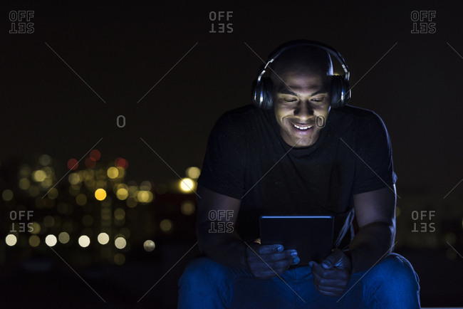 Happy mid adult man using digital tablet and wireless headphones at night