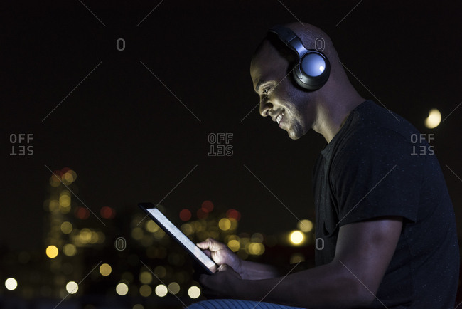 Side view of mid adult man using wireless headphones and digital tablet at night