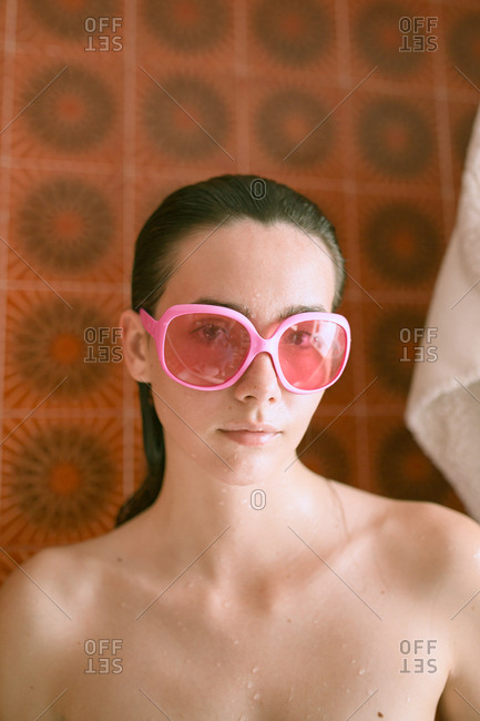 Young brunette woman with pink retro eyeglasses relaxing on bath under neon colorful lights