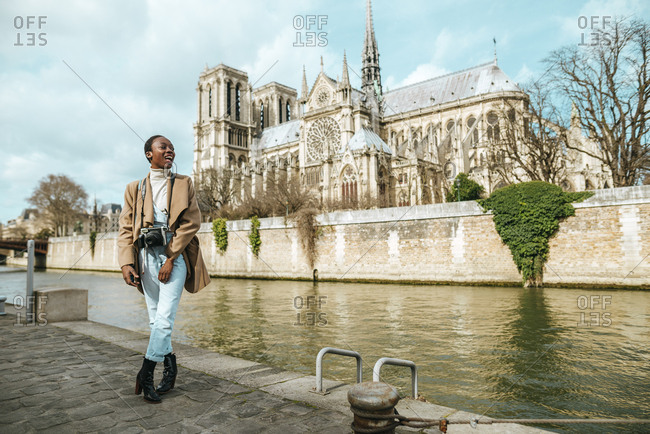 Woman with photo camera in front of Notre Dame Cathedral, Paris.