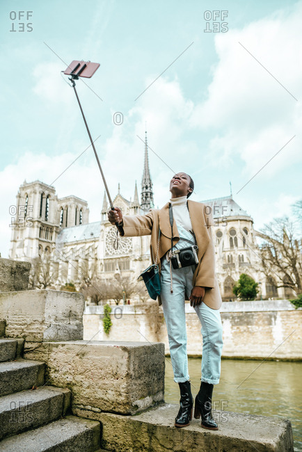 Tourist woman taking a selfie with the smartphone in front of Notre Dame, Paris.