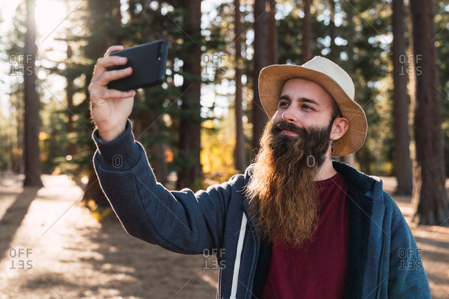 Smiling adult man with long beard taking selfie with smartphone in sunny woods of Lake Tahoe