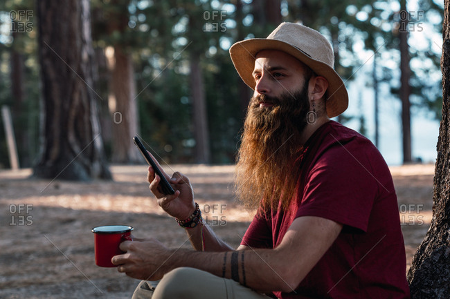 Adult bearded man in hat holding cup of hot tea and smartphone looking away in sunlight, Lake Tahoe