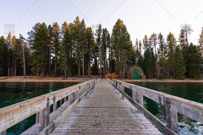 Perspective view of wooden pier on Lake Tahoe with green coniferous trees on shore, USA