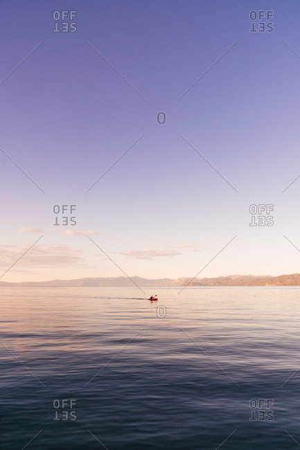View of small figure of boat sailing on peaceful water of Lake Tahoe under blue sky in twilight, USA