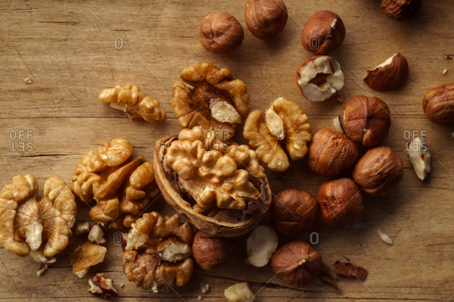 Variety of raw uncooked nuts with nutshells on wooden background. Overhead view with copy space