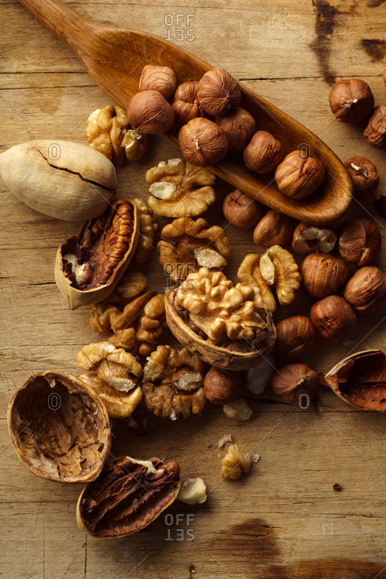 Variety of raw uncooked nuts with nutshells on wooden background. Top view