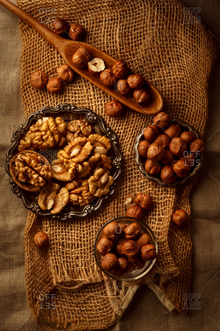 Top view image of raw hazelnuts and walnuts in wooden spoon and three bowls on a piece of rough linen cloth