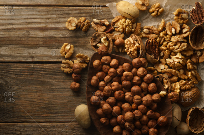 Variety of raw uncooked nuts with nutshells on wooden background. Top view with copy space