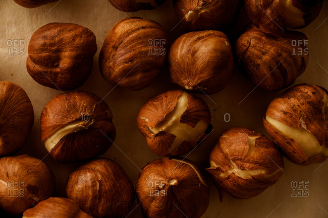 Roasted hazelnut with cracked skin on parchment paper
