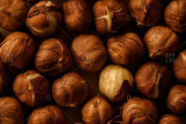 Roasted hazelnut with cracked skin on parchment paper with one nut peeled. Ingredient concept