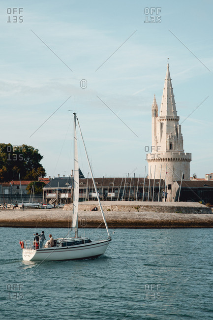 La Rochelle, France: 25 August 2018: Embankment at the La Rochelle city on the coast of Atlantic ocean. Medieval lighthouse built in gothic style