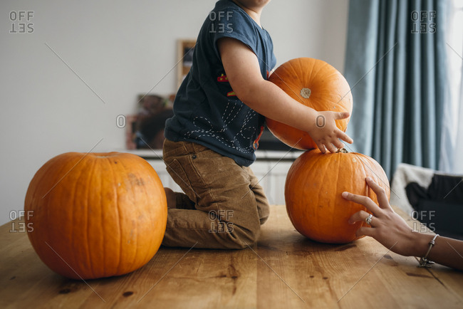 Kid playing with pumpkins on table