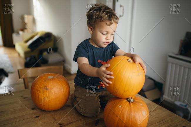 Kid piling up pumpkins on table