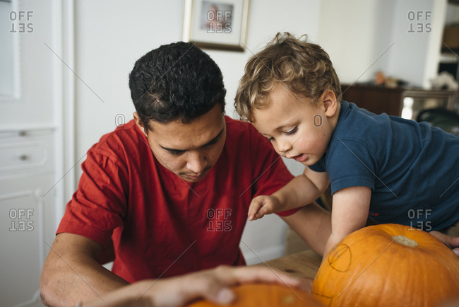 Boy pointing at drawing on pumpkin