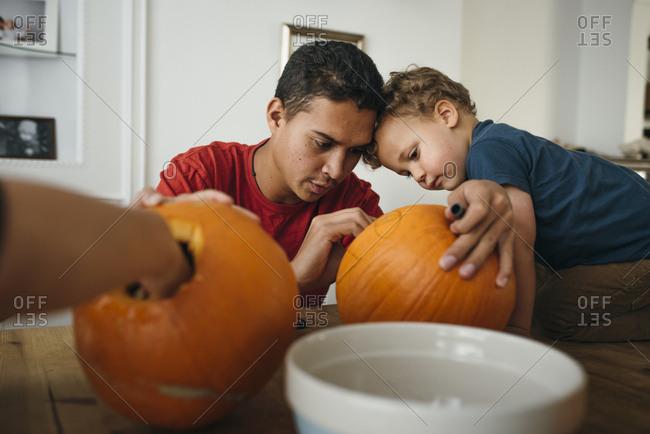 Boy looks at man drawing face on pumpkin