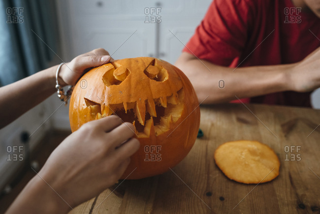 Woman hands carving Halloween pumpkin on table