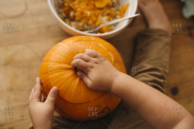Hands holding Halloween pumpkin on table