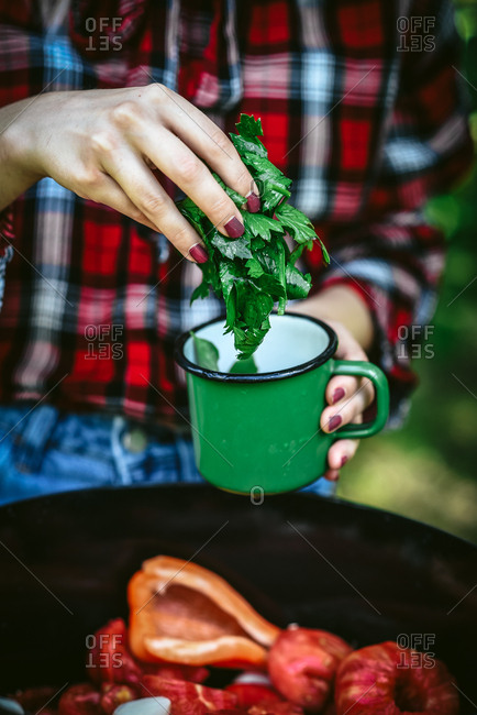 Woman putting vegetables into a green cup