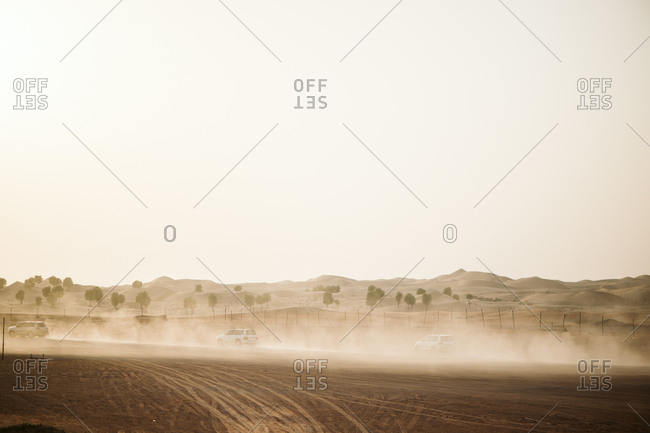 Cars stirring up dust in desert