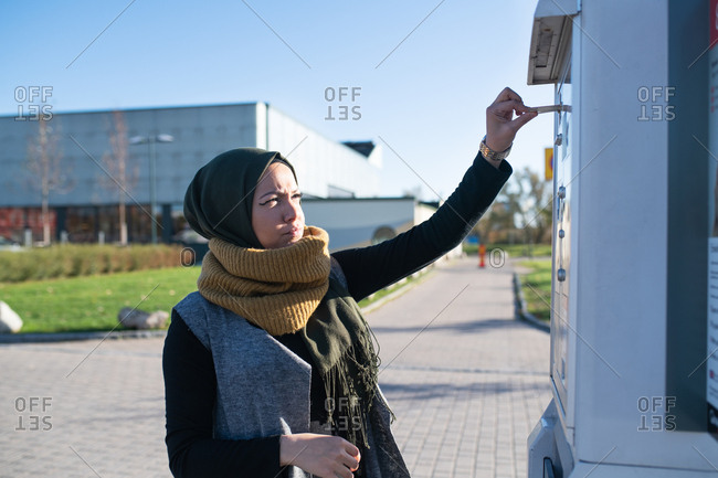 Woman wearing headscarf putting credit card into outdoor machine
