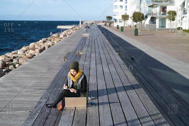 Woman wearing headscarf sitting beside ocean using laptop computer
