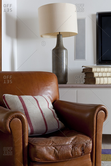 Modern leather chair and lamp with antique books