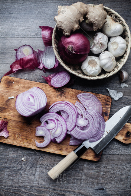 Chopped fresh red onion and knife on wooden cutting board alongside basket with ginger and garlic
