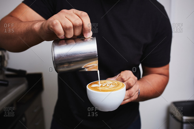 Barista pouring milk into coffee to create latte art