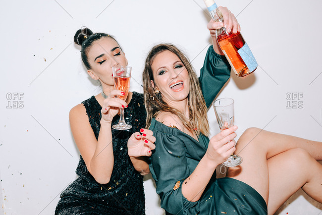 Two girlfriends celebrating New Year's Eve and drinking champagne together