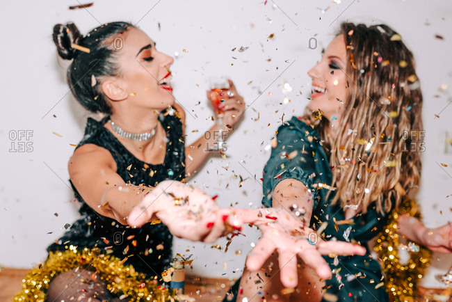 Two girlfriends celebrating New Year's Eve and throwing around confetti