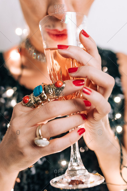 Woman in black sequin dress holding a glass of champagne wrapped in New Year's decoration light bulbs