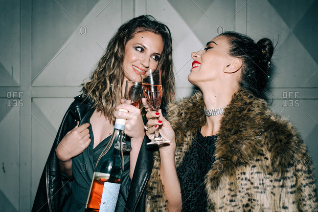 Two dressed up friends having fun drinking champagne and laughing outdoors at night