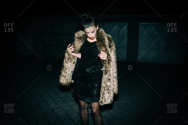 Woman in black sequin dress and faux fur coat outdoors at night