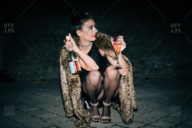 Smiling woman wearing black sequin mini dress and faux fur coat squatting and holding a bottle and glass of champagne outside at night