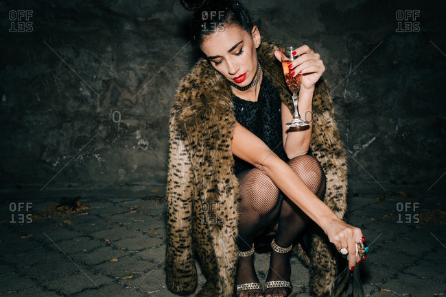 Woman wearing black sequin mini dress and faux fur coat in squat position holding a bottle and a glass of champagne outdoors at night