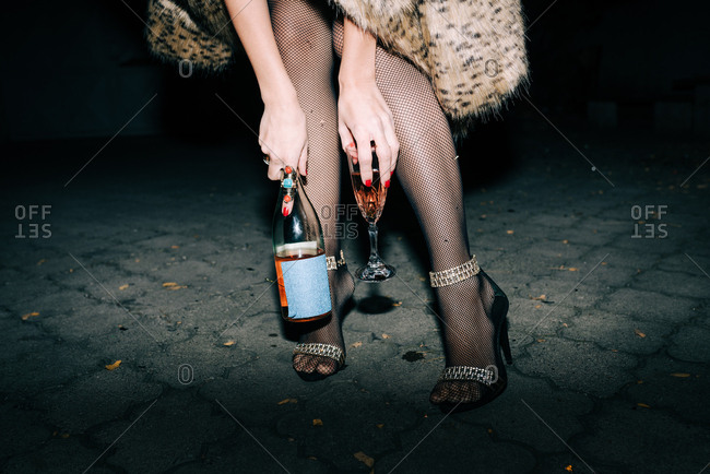Woman in faux fur coat and high heels holding a bottle and a glass of champagne outside at night