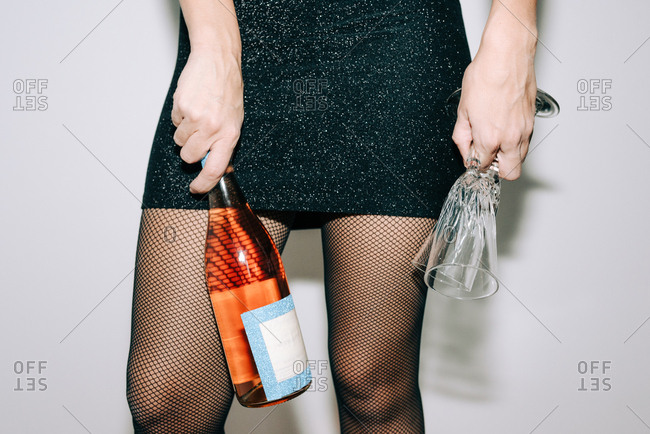 Woman dressed up for party holding a bottle and champagne glasses