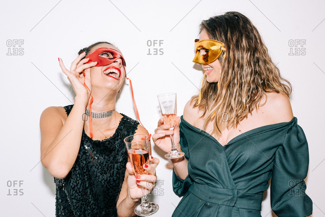 Two dressed up women celebrating New Year's Eve and having fun while drinking champagne and putting masks on their faces