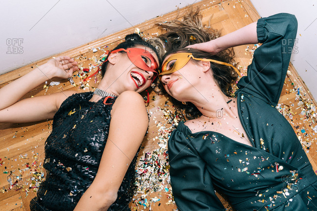 Two dressed up women wearing masks laying on the floor on confetti and having fun