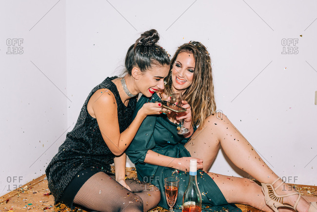 Two laughing women celebrating New Year's Eve and wishing a happy New Year to someone on the phone