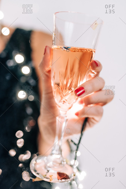 Close up of woman wrapped in decorative light bulbs for New Year's and holding a glass of champagne