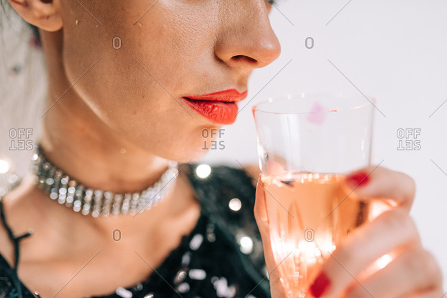 Woman holding a glass of champagne to her lips at New Year's Eve party