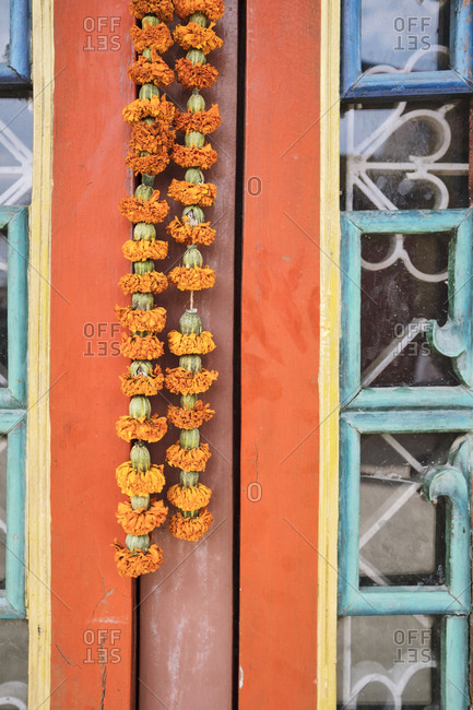 Marigold garland hanging by colorful door
