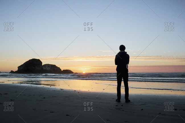 Silhouette of man watching sunset on beach